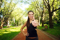 Young fit sportive woman shows hands with thumbs up happily Stock Images