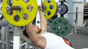 Young fit sportsman doing barbell bench pressing while exercising at fitness club. Muscular man exercising in the gym stock photography