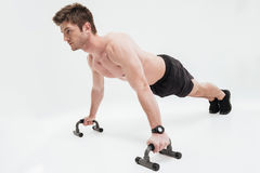 Young fit sportsman doing push ups with bars stock photo