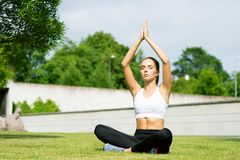 Young, fit and sporty girl doing yoga exercise meditation in the park. Fitness, sport, urban and healthy lifestyle. Young, fit and sporty woman doing yoga Stock Images