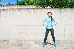 Young, fit and sporty girl in the street. Fitness, sport, urban jogging and healthy lifestyle concept. Stock Image
