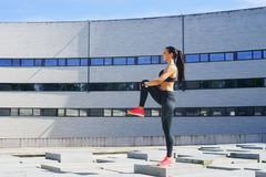Young, fit and sporty girl in the street. Fitness, sport, urban jogging and healthy lifestyle concept. Royalty Free Stock Photography