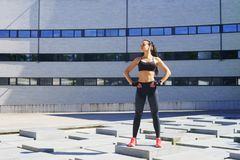 Young, fit and sporty girl in the street. Fitness, sport, urban jogging and healthy lifestyle concept. Royalty Free Stock Images
