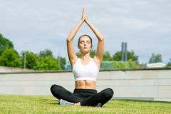 Young, fit and sporty woman doing yoga exercise meditation in the park. Fitness, sport, urban and healthy lifestyle. Young, fit and sporty girl doing yoga Royalty Free Stock Photos