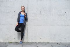 Young, fit and sporty woman. Fitness, sport, urban and healthy lifestyle concept. Young, fit and sporty woman standing in front of concrete cement wall. Fitness royalty free stock images
