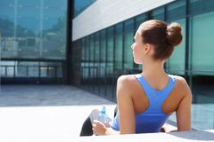 Young, fit and sporty girl preparing for urban jogging. Fitness, sport and healthy lifestyle concept. Young, fit and sporty woman resting after the training stock photography