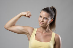 Young fit sporty woman in singlet with ponytail flexing biceps arm muscle looking at camera Stock Photos