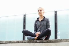 Young, fit and sporty woman sitting on a concrete border. Fitness, sport, urban jogging and healthy lifestyle concept. Stock Image