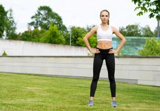 Young, fit and sporty woman stretching in the park. Fitness, sport, urban and healthy lifestyle concept. Young, fit and sporty girl stretching in the park stock photos