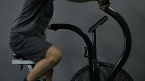 Young Fit Tanned Man Working Out on Exercise Air Bike
