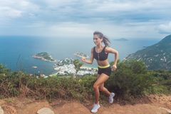 Young fit tanned woman trail running up the steps carved into the hillside with mountains, sea, islands and cloudy sky stock photos