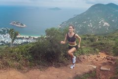 Young fit tanned woman trail running up the steps carved into the hillside with mountains, sea, islands and cloudy sky royalty free stock image