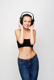 A young and fit teenage girl listening to music in headphones Stock Images