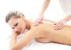 A young and fit woman on a back massage procedure Stock Image