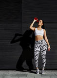 Young fit woman with beautiful figure refreshing with energy drink against black wall in the city Royalty Free Stock Photography