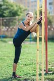 Young fit woman in a blue shirt and leggings training outdoors at sunset. Fitness woman doing stretching on wall bars. Healthy lif royalty free stock images