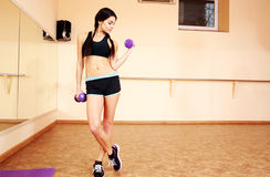 Young fit woman doing exercises with dumbells. At gym Royalty Free Stock Photography