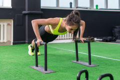 Young fit woman doing horizontal push-ups with bars in gym. Young fit woman doing horizontal push-ups with bars in gym royalty free stock photography