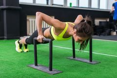 Young fit woman doing horizontal push-ups with bars in gym. Stock Photo
