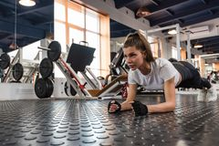 Attractive young woman does plank exercise in gym. Young fit woman doing plank exercise in modern gym royalty free stock photography