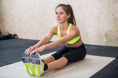 Young fit woman doing seated forward fold exercise, sporty female stretching stock photos