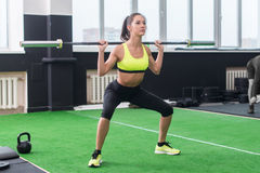 Young fit woman doing squats with barbell, exercising back and legs muscles Stock Image