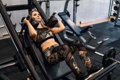 Young fit woman doing workout exercise in gym stock photo