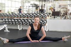 Young fit woman doing yoga gymnastics at gym. Pretty smiling woman doing split on mat at gym and looking at camera. Sound mind in a sound body royalty free stock photography