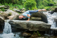 Young fit woman doing yoga oudoors at waterfall Royalty Free Stock Photography