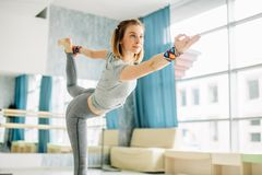 Young fit woman doing a yoga pose standing with one leg raised up. royalty free stock photography