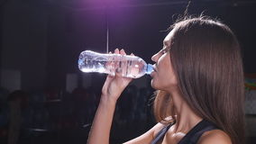 Young fit woman drinking water at gym stock footage