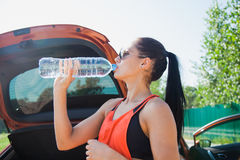 Young fit woman drinks water near car after hard workout outdoors. Healthy active lifestyle concept Stock Photos