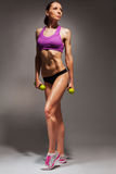 Young fit woman with dumbbells exercise Royalty Free Stock Image