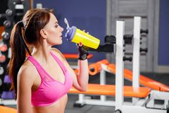 Young fit woman with energy drink relaxing and drinking in the gym. Sport and fittness concept.  Royalty Free Stock Photography