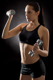 Young fit woman exercise weights on black Stock Photography
