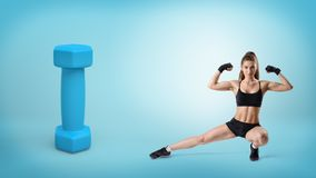 A young fit woman in fitness closing sits in a low side lunge near a giant blue dumbbell. Stock Images