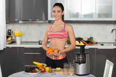 Young fit woman with fruits, in the kitchen Stock Photo