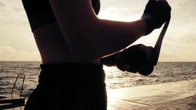 Young fit woman getting her fists ready for the boxing gloves by wrapping bandage around them standing against the sun stock footage