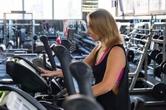 Young fit woman at the gym using elliptical cross trainer. Female gymnast at a fitness room working out on an exercise bike royalty free stock photography