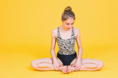 Young fit woman gymnast stretching in lotus pose Stock Photography