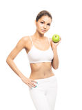 A young and fit woman holding a fresh green apple. Young, sporty, fit and beautiful girl with the apple isolated on white Royalty Free Stock Images