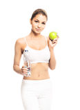 A young and fit woman holding a fresh green apple. Young, sporty, fit and beautiful girl with the apple isolated on white Stock Photos