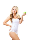 Young and fit woman holding a fresh green apple. Fit and sporty girl in white underwear. Beautiful and healthy woman eating green apple isolated on white Stock Photo