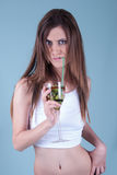 Young fit woman holding a glass with kiwi pieces Royalty Free Stock Image