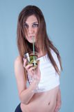 Young fit woman holding a glass with kiwi pieces Royalty Free Stock Photos