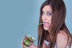 Young fit woman holding a glass with kiwi pieces Royalty Free Stock Photography