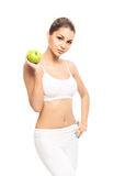 A young and fit woman holding a green apple Stock Images