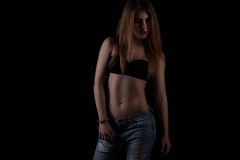Young fit woman in jeans, black background. Female with perfect abdomen muscles on black background Stock Photography