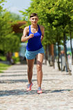 Young fit woman jogging in the city park. Royalty Free Stock Images