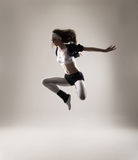 A young and fit woman jumping in sporty clothes Stock Photography